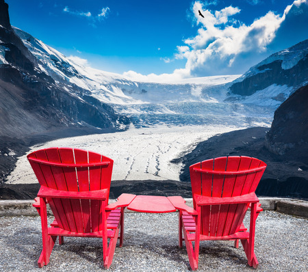 interconnected: Two red plastic chairs, interconnected, facing the famous glacier Columbia