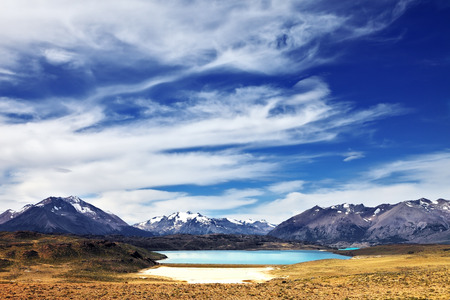 cloud capped: Charming lake in a valley surrounded by snow-capped mountains. The huge deserted National Park Perito Moreno in Patagonia, Argentina