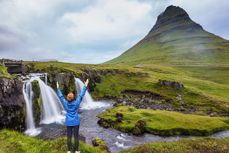 admires: Middle-aged woman tourist admires the beauty of nature. Threaded full-flowing waterfall Kirkjufell Foss on the grassy mountains