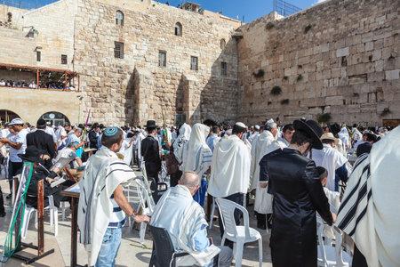 holies: JERUSALEM, ISRAEL - OCTOBER 12, 2014:  Morning autumn Sukkot. Huge crowd of faithful Jews wearing in white prayer shawls