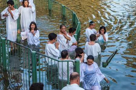 baptized: YARDENIT, ISRAEL - JANUARY 21, 2012: Christian pilgrims baptized in the Jordan River. They enter the water, dressed in special white robes