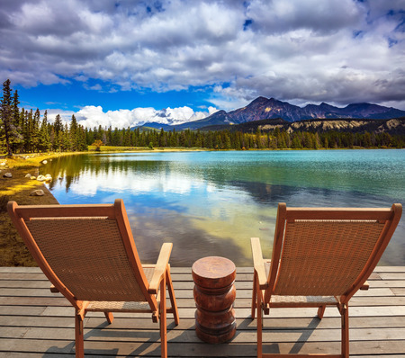 round chairs: Two comfortable lounge chairs on wooden pedestal on the lake. Round lake in the coniferous forest. Canadian Rocky Mountains