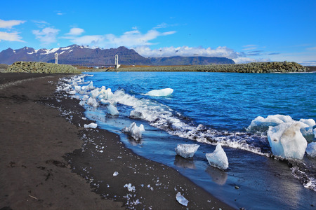 ice floes: Ocean surf on the beach with black sand. Ice floes in the sun shine
