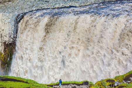 masses: The powerful waterfall Dettifoss in Jokulsargljufur National Park, Iceland. Elderly woman photographed waterfall. Huge masses of water cascading into the abyss