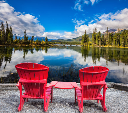 lounges: Two red chaise lounges for the tourists connected among themselves by a table. Pyramid Mountain reflected in Pyramid Lake
