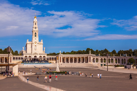 believers: Catholic Cathedral and colonnade in Fatima, Portugal. Believers and tourists walk on the square in front of the cathedral