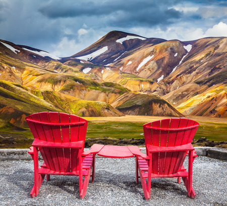 lounges: Two convenient red chaise lounges connected by small table stand for tourists Stock Photo