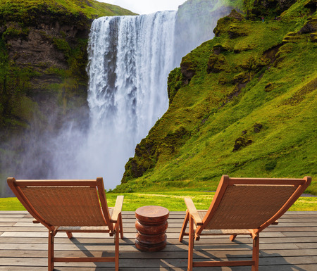 deck chairs: Magnificent famous waterfall Sk�gafoss, Iceland. A powerful jet Sk�gar river falls from  large glacier. On stony ground in front of the waterfall are two wooden deck chairs