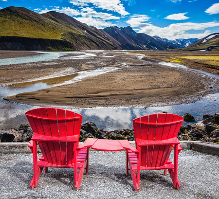 lounges: Multi-colored mountains from mineral rhyolite are lit with sun. Two red chaise lounges stand for tourists