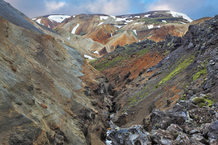 hollows: Pieces of gray and black lava, sometimes covered with green moss. In the background -  orange and blue rhyolite mountains. National Park Landmannalaugar in Iceland Stock Photo