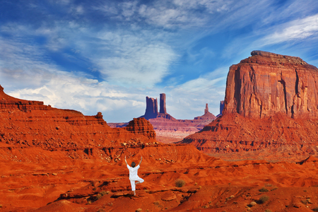 mitts: Navajo Reservation in the US. Red Desert and rocks - mitts sandstone. Woman in white performs asana Tree