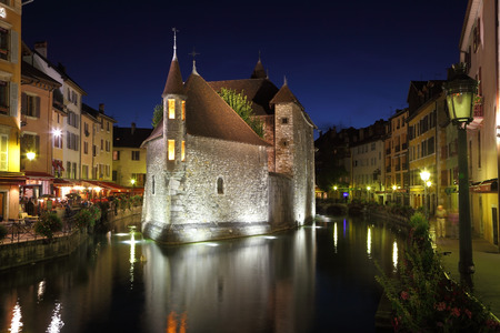 ancient prison: The capital of the Haute-Savoie - Annecy. The main attraction of the city - an ancient fortress-prison on an island in the middle of the river. Fortress beautifully lit and is reflected in the smooth water.