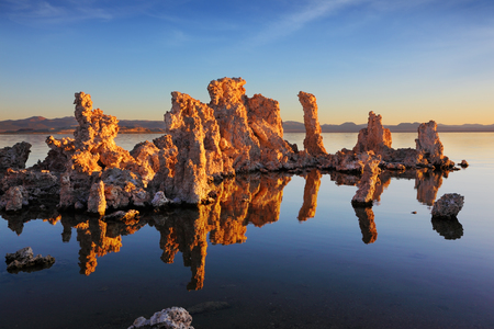 sal: Orange sunset on Mono Lake. Outliers - bizarre calcareous tufa formation  reflected in the smooth water.