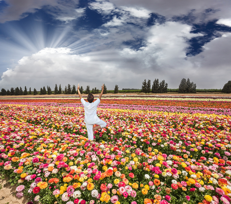 kibbutz: Flower kibbutz near Gaza Strip. Spring flowering buttercups. Delighted woman in white greets the rising sun Stock Photo