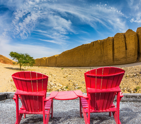 lounges: Two convenient red chaise lounges connected by small table stand for tourists. Walking route on  picturesque Black canyon Stock Photo