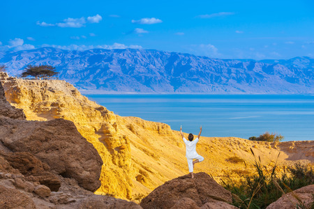 gedi: Elderly woman practices yoga on a rock near the Dead Sea. Travel national parks and reserves Ein Gedi, Israel Stock Photo