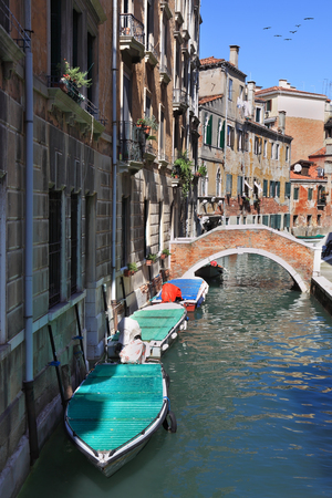 shined: Eternal fantastic Venice. The narrow street - channel is brightly shined by the midday sun. At a wall gondolas are moored Stock Photo