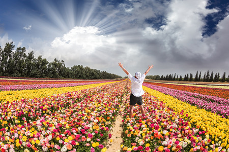 strip shirt: Flower kibbutz near Gaza Strip. Spring flowering buttercups. Stunned tourist in white shirt and bandana greets the rising sun