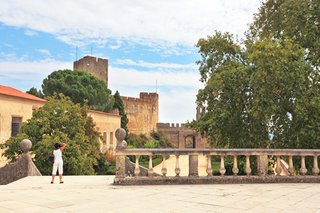 templars: The imposing medieval castle - the monastery of the Templars. A woman dressed in white photographs in the park