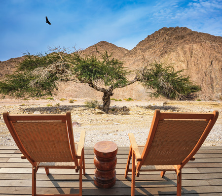 lounges: Two convenient chaise lounges and small table stand for tourists. Walking route on  picturesque Black canyon