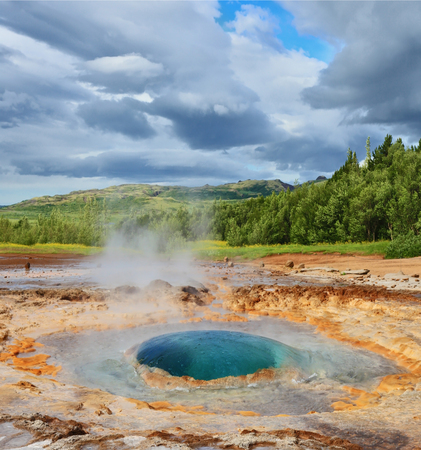 fumarole: Magnificent geyser Strokkur in Iceland. Bowl-shaped fumarole depression in the ground with splashing hot water azure