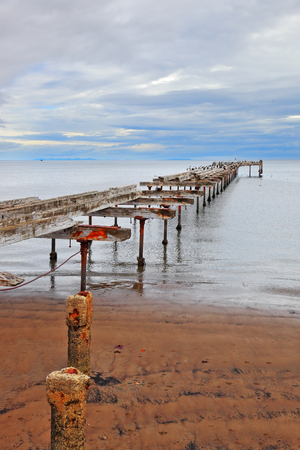 strait of magellan: Old dilapidated pier in the Strait of Magellan. Corroded bearings and collapsed wooden flooring