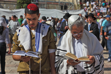 religious clothing: Jerusalem - October 16: The Holy Western Wall of the Temple. Jewish family - the father of religious clothing and his son, a soldier in uniform, praying in the square near the Wailing Wall in Sukkot, October 16, 2011 in Jerusalem, Israel Editorial