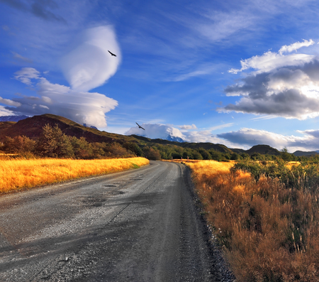 impressive: The impressive cloud over Patagonia. Amazingly beautiful sunset illuminates the distant mountains and the dirt road with bright light Stock Photo