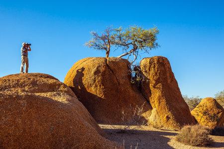 arcos de piedra: reserva natural Spitzkoppe. Los pintorescos arcos de piedra pintadas de rojo y naranja. El fot�grafo toma el paisaje m�gico Editorial