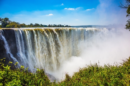 The famous Victoria Falls on the Zambezi River in South Africa. At the end of the rainy season, the waterfall most high water Фото со стока