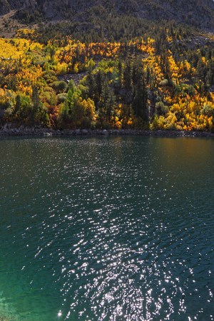 midday: Mountain fishing lake with transparent azure water. Solar autumn midday