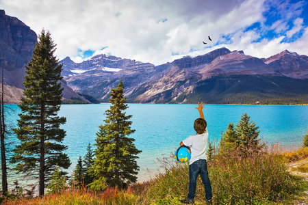 admire: Bow Lake glacial lake in the Banff National Park in the Canadian Rockies. The seven-year slender boy with the globe in hands admire the beauty of nature.