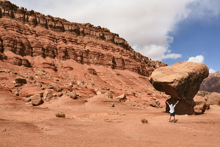 giant mushroom: The admired tourist before a grandiose rock from red sandstone. USA