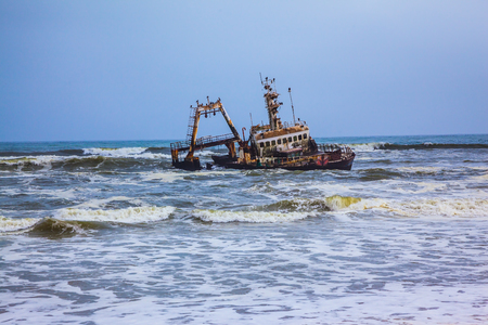 The ship crashed in Skeleton Coast in Namibia many years ago. Rough surf of the Atlantic Stock Photo