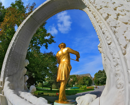 gilded: Elegant gilded statue of Johann Strauss, playing the violin in white marble arch. Park in Vienna Editorial
