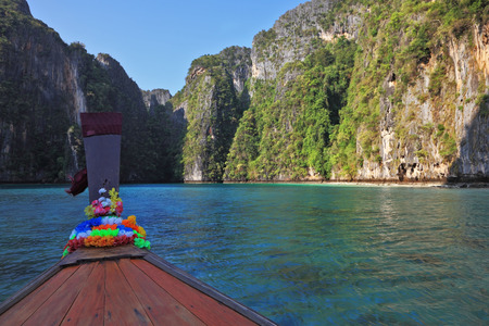 sciarpe: Thailand sightseeing boat sails in the picturesque bay. Bow is decorated with colorful and bright silk scarves Archivio Fotografico