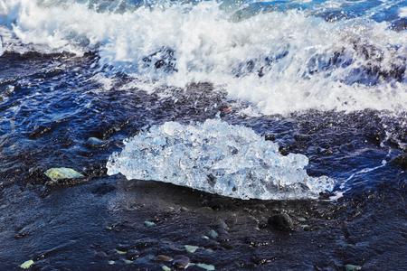 ices: The Arctic Ocean. Iceland. Floating ices Yokulsaurloun lagoon on the beach with black sand