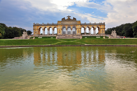 Schönbrunn - the summer residence of the Austrian Habsburgs. Magnificent colonnade reflected in the smooth water of the pond