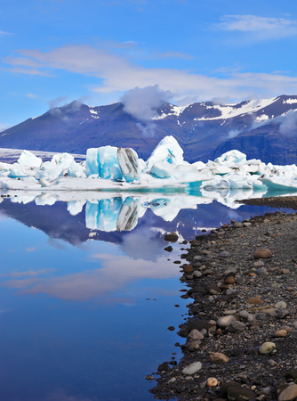 ice floes: Reflection. Sunrise.  Blue and turquoise icebergs and ice floes are reflected in smooth water of the Gulf J?kuls?rl?n in Iceland Stock Photo