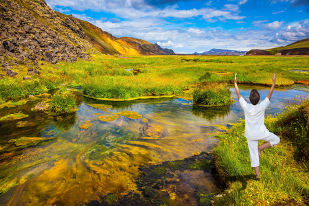 The elderly woman carries out pose of Tree in yoga among thermal sources. The picturesque valley in Landmannalaugar national park Stock Photo