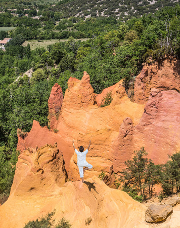 roussillon: Orange and red picturesque hills in Roussillon. The elderly woman in special form of yoga  performs asana Tree