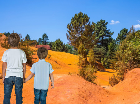 admired: Two boys of seven and four years admired the nature. Orange and red picturesque hills. Languedoc - Roussillon, Provence, France Stock Photo