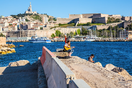 sea seaport: MARSEILLE, FRANCE - MAY 22, 2015: The morning rehearsal. Girls playing on guitar at sea pier. Old seaport