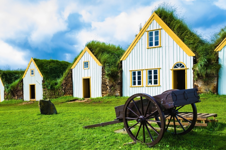 reconstituted: The village first settlers in Iceland. The reconstituted village - Pioneer Museum - Viking. Old wooden two-wheeled carriage on front lawn of the house