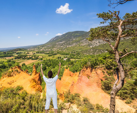 roussillon: The elderly woman performs yoga in special form. Orange and red picturesque hills in Roussillon