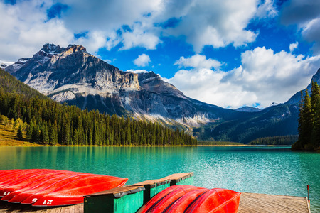 activ: Shiny red kayaks are dried upside down. Emerald Lake in the Canadian Rockies. The concept of leisure and tourism