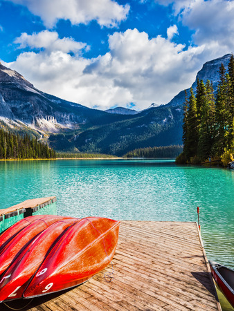 activ: The concept of active tourism and vacation. Emerald Lake in the Canadian Rockies. Shiny red kayaks are dried upside down Stock Photo