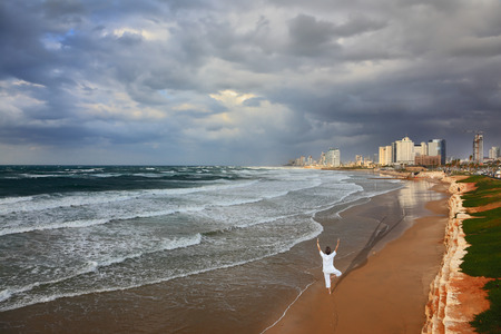 Storm cloud hanging over the sea, the woman in white performs asana Tree on one leg. Promenade and beach in Tel Aviv