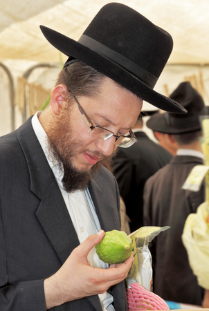 skullcap: BNEI- BRAK, ISRAEL - SEPTEMBER 17, 2013: Traditional market before the holiday of Sukkot. Religious Jews in black hats and skullcap of carefully selected ritual fruits and plants