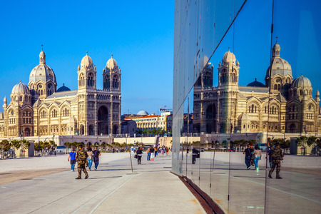 major ocean: MARSEILLE, FRANCE - MAY 22, 2015:  Sunny spring morning in Marseille. Cathedral of Saint Mary Major is reflected in the mirrored wall of a building